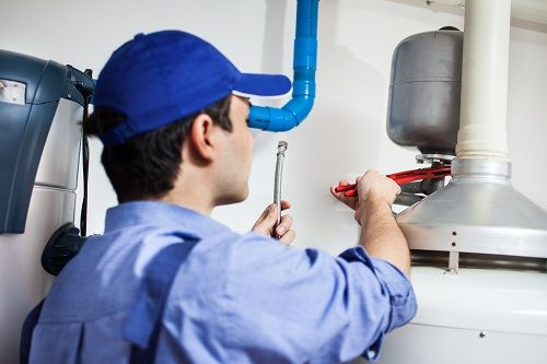 Plumber inspecting water heater